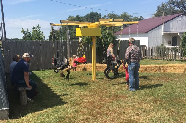 Group of people playing on the tire swings.
